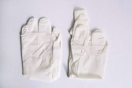 Pair of medical white latex protective gloves on white background. Protective disposable gloves against the spread of virus, flu, coronavirus (COVID-19), bacterial. Health care and surgical concept.