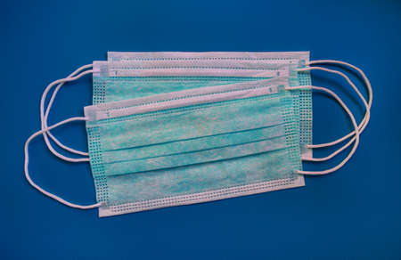 Medical protective green masks activated carbon disposable fiber face on blue background. Face masks that covers mouth and nose, that protects against virus, flu, coronavirus (COVID-19), bacterial.