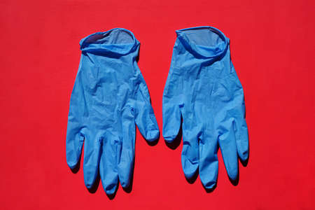 Pair of medical blue latex protective gloves on red background. Protective disposable gloves against the spread of virus, flu, coronavirus (COVID-19), bacterial. Health care and surgical concept. Stock Photo - 153185302