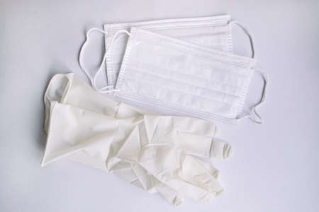 Medical protective disposable white masks and glove on white background. Protection equipment against virus, flu and coronavirus (COVID-19), bacterial and germs. Health care and surgical concept.