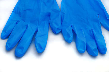 Pair of medical blue latex protective gloves on white background. Protective disposable gloves against the spread of virus, flu, coronavirus (COVID-19), bacterial. Health care and surgical concept.
