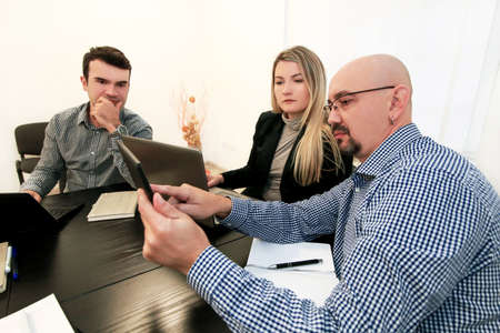 Business team meeting in their modern office. They develops business development plan and ideas. Business people working together on laptop and tablet, talk and creative communicate of next projects. Stock Photo