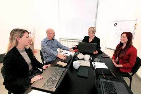 Business men and women at the meeting. Corporate group. Full concentration at work. Group of business people working and communicating while sitting at office desk together with colleagues sitting. Stock Photo