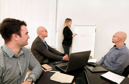 Businesswoman and leader team use white board drawing explains colleagues graph of development business plan and creative ideas in modern office. Business team meeting and full concentration at work.
