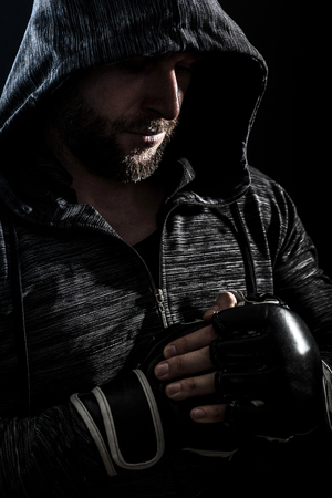 Studio shot of male boxer on black background.