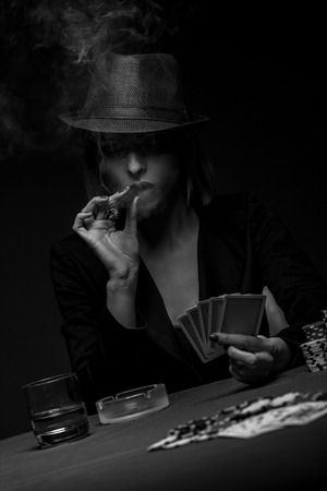 Beautiful young woman playing poker on isolated black background.