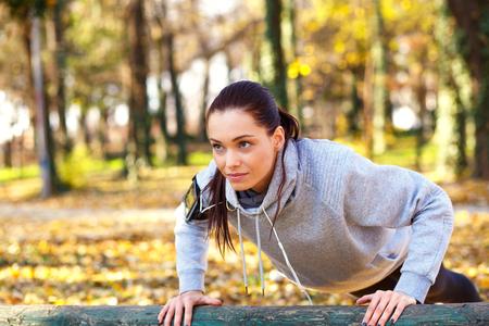 Attraktive sportliche Frau mit Kopfhörern, die draußen im Park Liegestütze macht.