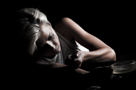 Studio shot of young woman injecting drug. Model poses as drug addict.