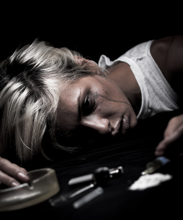 Disparo de estudio de una mujer joven que se inyecta drogas. Modelo se hace pasar por adicto a las drogas.