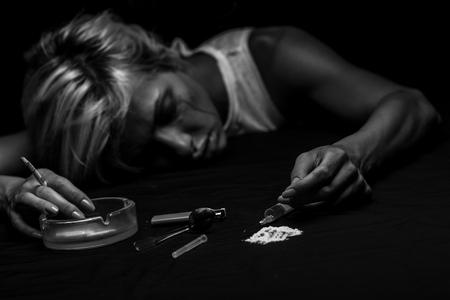 Studio shot of young woman injecting drug. Model poses as drug addict. Reklamní fotografie