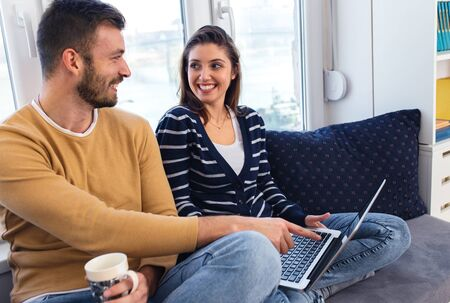 Young couple spending time together at home, they siting by the window and using at laptop.