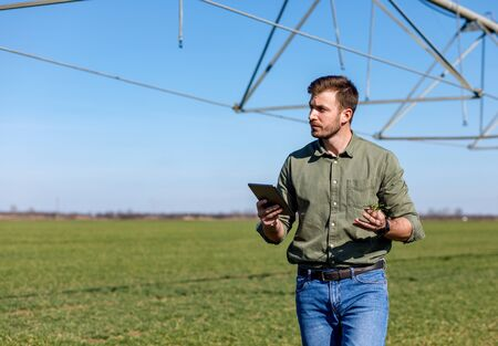 Young farmer standing in wheat field and setup irrigation system on tablet.