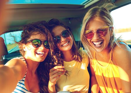 Three female friends enjoying traveling in the car. Sitting in rear seat and and making selfie. Standard-Bild