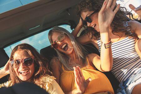Three female friends enjoying traveling in the car. Sitting in rear seat and having fun on a road trip. Standard-Bild