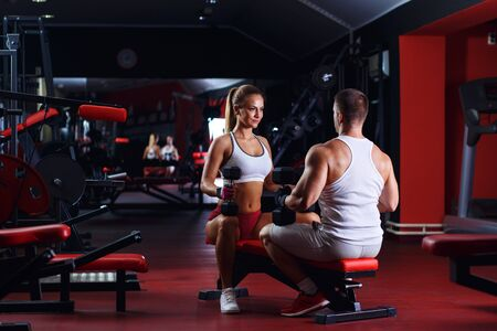 Fitness couple exercising with dumbbell weights in the gym. Reklamní fotografie