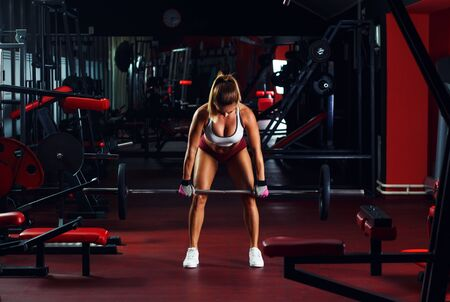 Young woman exercising with barbell weight in the gym. Standard-Bild