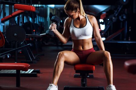 Young woman exercising with weight in the gym. Standard-Bild