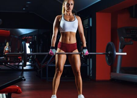 Young woman exercising with barbell weight in the gym. Reklamní fotografie
