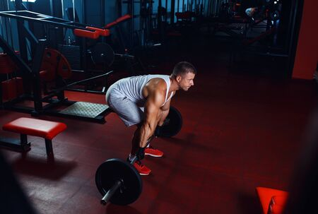 Young man exercising with barbell weight in the gym.