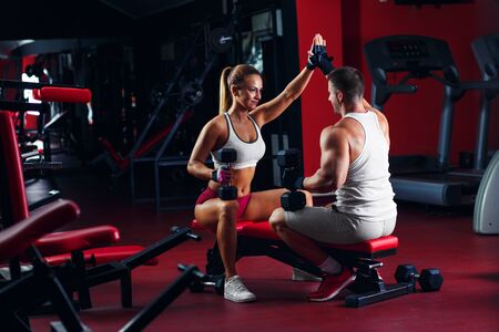 Fitness couple exercising with dumbbell weights in the gym. Standard-Bild