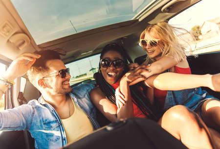 車の中を旅行し、後部座席に座って、ロードトリップでたくさんの楽しみを楽しむ3人の親友。 写真素材