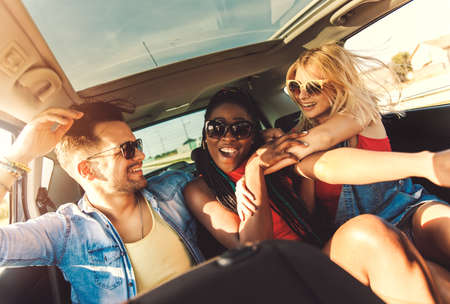 Three best friends enjoying traveling in the car, sitting in rear seat and having lots of fun on a road trip. Stock Photo