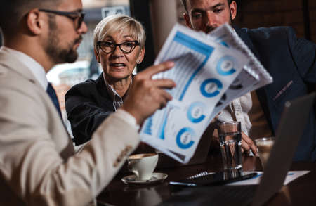 Senior businesswoman holding a meeting with her younger colleagues at office cafeteria. Standard-Bild