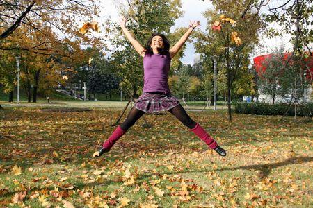 Joyful woman jumping in autumn park  Stock Photo