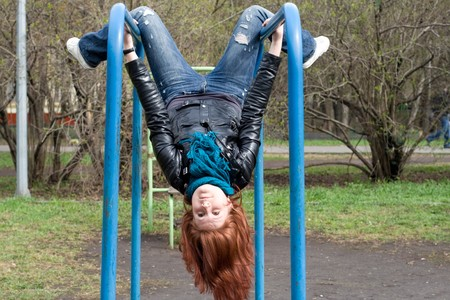 cool down: Sportive girl hanging on horizontal bar outdoor