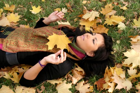 Pretty young woman lying on a carpet of leaves in autumn park  photo