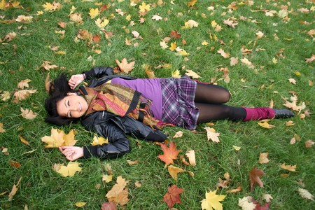 Happy woman lying on a carpet of leaves in autumn park  photo
