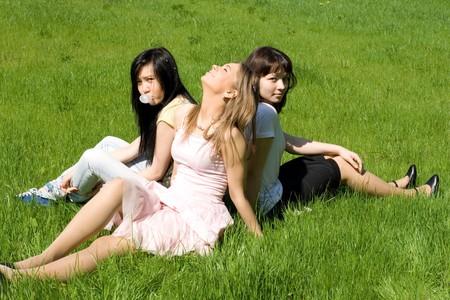 Three girls sitting on grass photo
