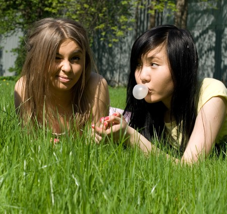 Two girls lying on grass photo