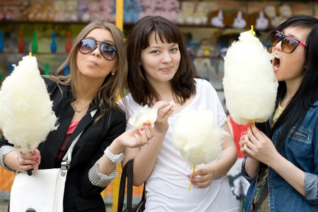 Three girls eating candy floss photo