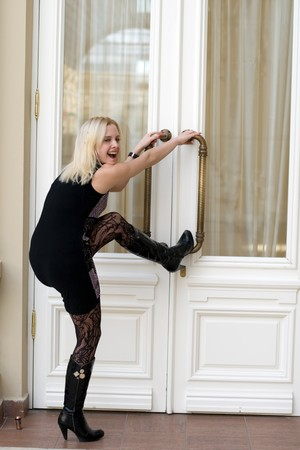 Funny young woman trying to open doors