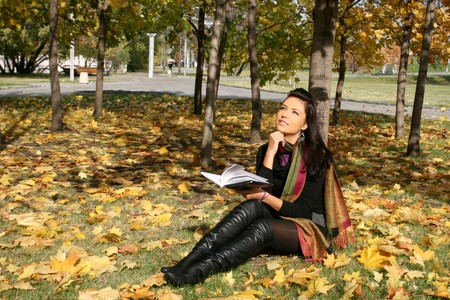 Smiling woman reading a book in autumn park  photo