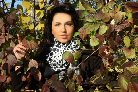 Beautiful young woman standing among leaves photo