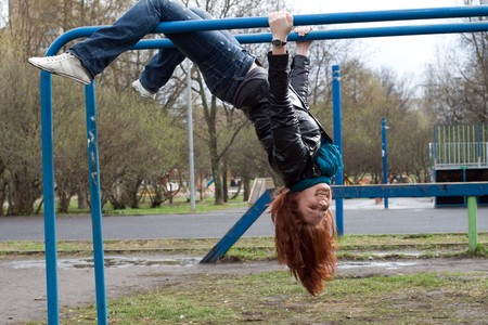 hanging woman: Sportive girl hanging on horizontal bar outdoor
