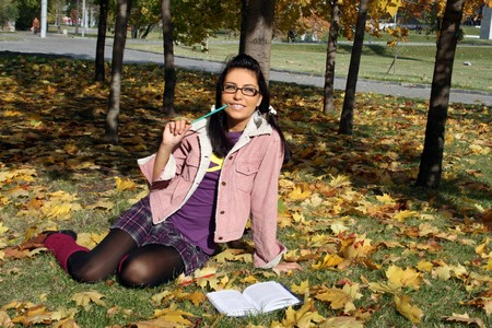Funny college girl studying in autumn park