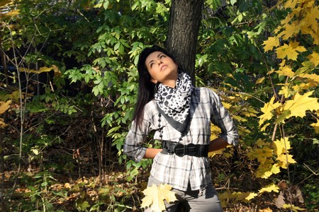 Beautiful young woman standing among leaves in forest  photo