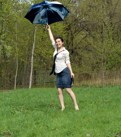 Business woman jumping with umbrella Stock Photo - 7106315