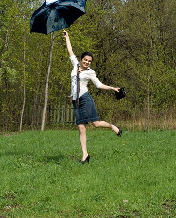 Business woman jumping with umbrella photo