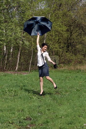 Business woman jumping with umbrella Stock Photo - 7106331