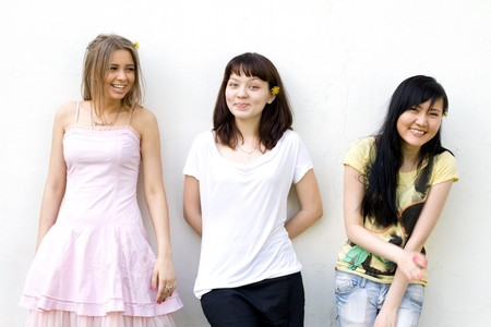 Three female friends standing in front of a white wall photo