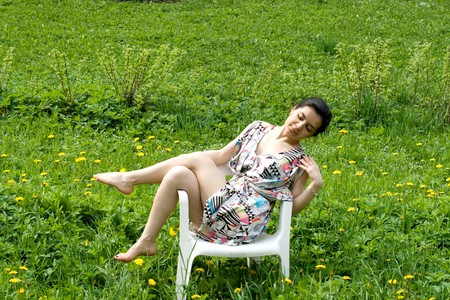 Girl resting in a chair among dandelions photo