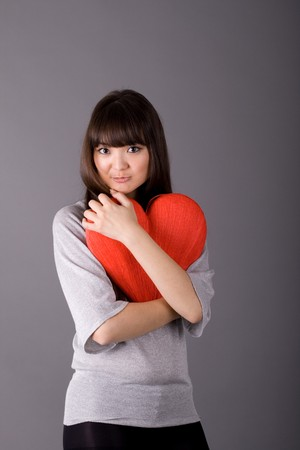 Beautiful woman holding red heart photo