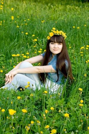 Girl sitting among dandelions photo