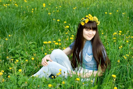 Girl sitting among dandelions Stock Photo - 7212302