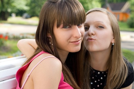 Two female friends sitting on bench photo