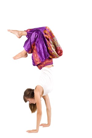 Girl in ethnic clothes standing on hands photo